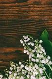 Skogen blommar liljekonvaljer på en bakgrund av bruna träbräden Arkivbild