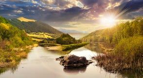 Skogflod med stenar och gräs på solnedgången Royaltyfri Fotografi
