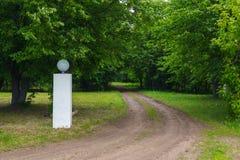 Skoggrusväg och vit pol Royaltyfri Fotografi