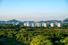 Skoglandskap med andelsfastigheter i bakgrunden, nära Vila Panam arkivfoto