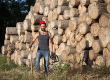 Skogsarbetare med chainsawen och yxa i skog Royaltyfria Foton