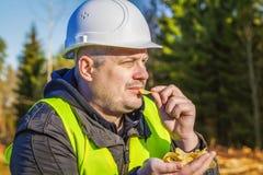 Skogsarbetare med potatischiper i skogen Arkivfoton