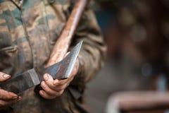 Skogsarbetaren som rymmer en yxa och, gör den skarpare Arkivfoton