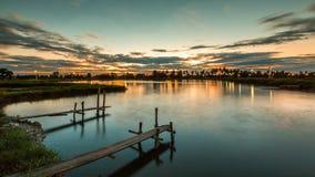 Skogsbevuxen bro i porten på solnedgången royaltyfria foton