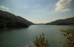 Skogsbevuxet berg- och flodlandskap Arkivfoton