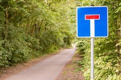 Skogväg med tecknet som ett tecken för en återvändsgränd fotografering för bildbyråer