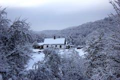 Skogvaktares stuga i en snöig skog i vinter Huntsman'sens hus bland träden som täckas med insnöat vintern royaltyfri foto