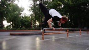Skoki do parku treningowego dla sportowców w parku miejskim Program Acrobat ćwiczy działanie bez ograniczeń Człowiek robiący smyk zdjęcie wideo