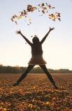 Skokowa nastoletnia dziewczyna, miotanie liście w powietrzu fotografia royalty free