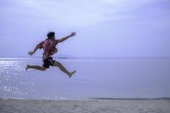 Skokowy młody człowiek w piasku przeciw morzu obrazy stock