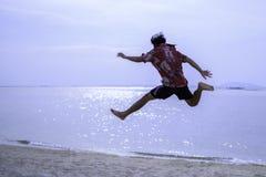 Skokowy młody człowiek w piasku przeciw morzu zdjęcia stock