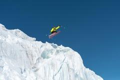 Skokowy narciarki doskakiwanie od lodowa przeciw niebieskiemu niebu w górach - wysoko Fachowy narciarstwo zdjęcia stock