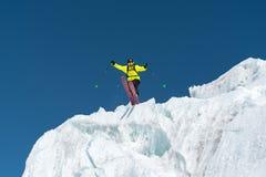 Skokowy narciarki doskakiwanie od lodowa przeciw niebieskiemu niebu w górach - wysoko Fachowy narciarstwo fotografia royalty free