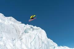 Skokowy narciarki doskakiwanie od lodowa przeciw niebieskiemu niebu w górach - wysoko Fachowy narciarstwo obrazy royalty free