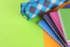 Skola anteckningsböcker av olika färger och ett blyertspennafall på en ljus apelsin och göra grön bakgrund täta tillförsel för ko royaltyfria foton