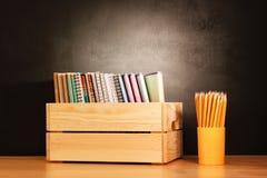Skola anteckningsböcker i rad i en träask och blyertspennor på ett träskolaskrivbord framme av en svart svart tavla books isolera royaltyfri fotografi