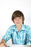 Skola den tonårs- pojken med blyertspennan som isoleras på vit Arkivfoto