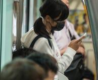 Skola flickan i Japan iklädd skolalikformig och den kirurgiska maskeringen på vägen till skolan Royaltyfri Bild