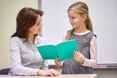 Skola flickan med anteckningsboken och läraren i klassrum Royaltyfri Bild
