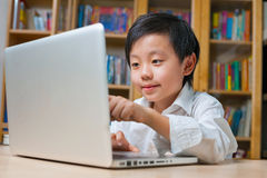 Skola pojken i vitskjorta framme av bärbar datordatoren Arkivbild