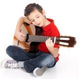 Skola pojken leker den akustiska gitarren Arkivfoto