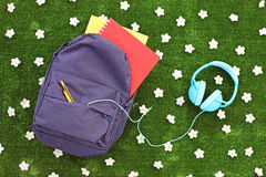 Skola ryggsäcken med böcker och hörlurar på ett gräs med tusenskönan arkivfoto