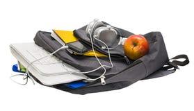Skola ryggsäcken med skolatillförsel och en minnestavla med headphonen Royaltyfri Bild