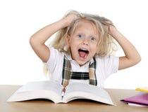Skola sött lite flickan som drar hennes blonda hår i spänningen som får galen, medan studera Royaltyfri Fotografi