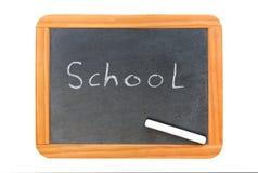 Skola skriftligt på den svart tavlan för tappning och en krita på brädet Arkivbilder