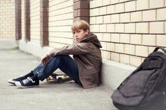Skola som är teen med schoolbagen och skateboarden royaltyfri bild