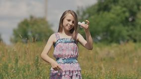 Skola ungeflickan som utomhus spelar med handspinnaren Populär och moderiktig leksak för händer för barn och vuxna människor stock video