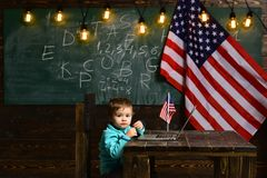 Skola ungen på kursen i 4th juli Pys med bärbara datorn för affär på amerikanska flaggan E-lära eller online-kurser Royaltyfri Bild