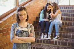 Skola vänner som trakasserar en ledsen flicka i skolakorridor Royaltyfri Bild