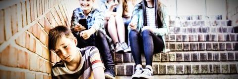 Skola vänner som trakasserar en ledsen pojke i skolakorridor royaltyfri bild