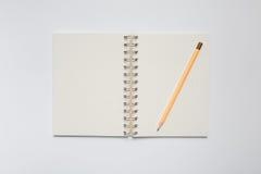 Skolaanteckningsbok med den gula blyertspennan Arkivfoton
