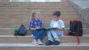 Skolaavbrott, pys och flicka att meddela och granska boken som sitter på skolamoment bredvid ryggsäckar i öppen luft arkivfilmer