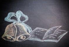 Skolabegrepp på den drog klockor och anteckningsboken för svart tavlakrita Arkivfoton
