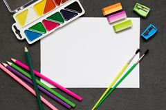 Skolabrevpapper på svart bakgrund, kulöra blyertspennor, pennor, plågor, papper, borstar för skolutbildning, kopieringsutrymme arkivfoton