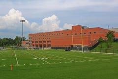 Skolabyggnad med fotbollfältet Arkivfoton