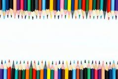 skolachildren& x27; s färgade blyertspennor lade ut i linje på en vit bakgrund royaltyfri foto