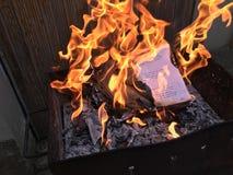 Skoladagbok med skriftlig anmärkningsbränning för daglig hand i brandflamma royaltyfri fotografi