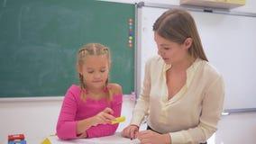 Skolaförberedelse, lärarekvinnahjälp till elevflickan att få kunskap genom att använda plast- diagram på tabellen nära svart tavl arkivfilmer
