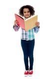 Skolaflicka en läsebok Royaltyfria Bilder