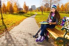 Skolaflicka med läroböcker i parkera Arkivbilder