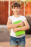 Skolaflickan rymmer en grön bok arkivfoton