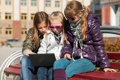 Skolaflickor som använder bärbara datorn på bänken Arkivfoton