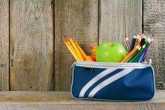 Skolahjälpmedel i ett fall På träbakgrund royaltyfri bild