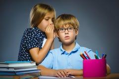 Skolakommunikationsbegrepp flicka som viskar i öra av pojken Arkivbild