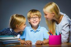 Skolakommunikationsbegrepp flickor som talar till pojken royaltyfri foto