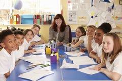 Skolaläraren och grupp som arbetar på projekt, ser till kameran arkivfoto